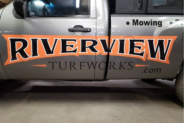 A closeup of the logo on the side of a Riverview Turf Turfwork's work truck.