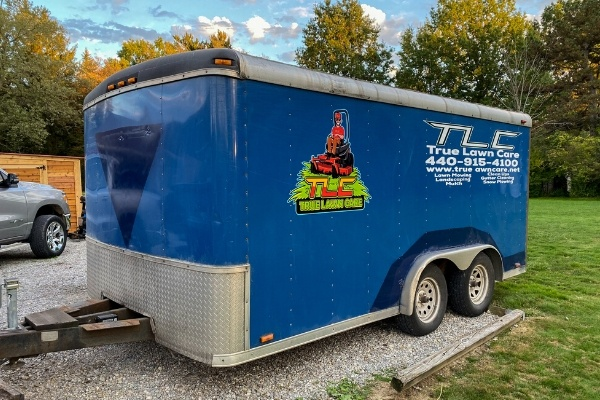 A True Lawn Care trailer with their phone number printed on the side.