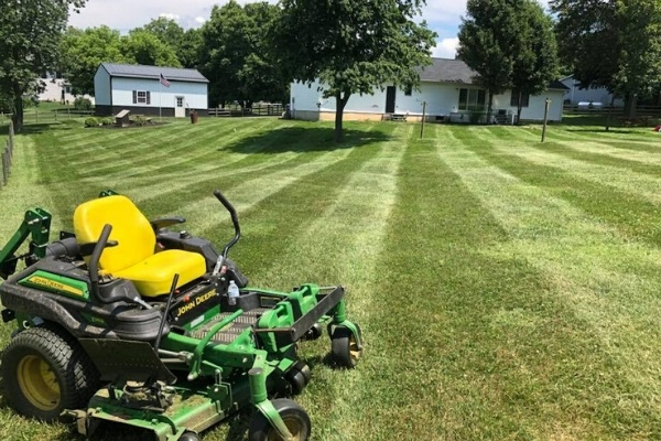 A commercial lawn mower sitting on a freshly mowed lawn.