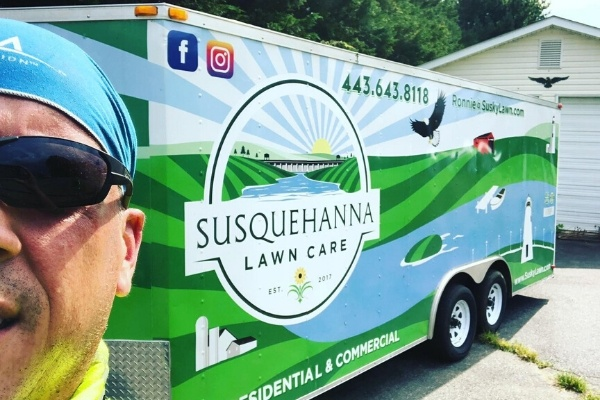 Owner of Susquehanna Lawn Care standing in front of a branded work trailer